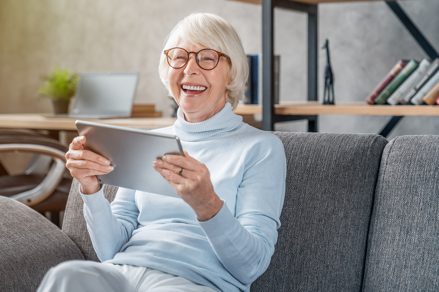 Senior Media Care - Seniorin mit Tablet in der Hand auf dem Sofa